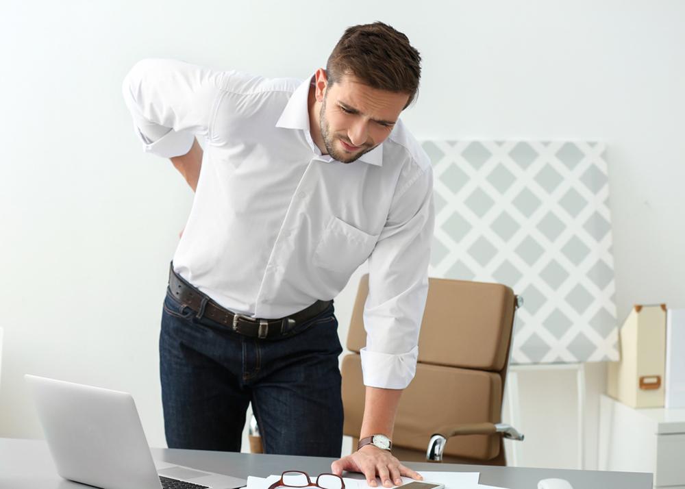 Mann mit chronischen Rückenschmerzen im Lendenwirbelbereich